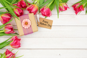 Corner border of pink flowers with Happy Mothers Day gift and tag against a rustic white wood background