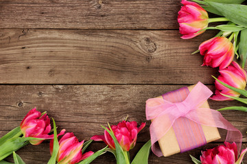 Corner border of pink flowers with gift box against a rustic dark wood background