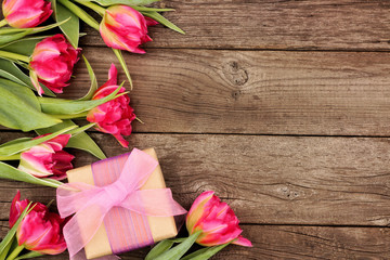 Side border of pink flowers with gift box against a rustic dark wood background