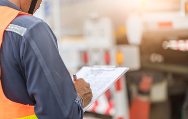 Preforming a pre-trip inspection on a truck,Concept preventive maintenance truck checklist,Truck driver holding clipboard with checking of truck,spot focus.