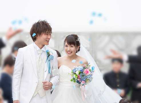 結婚式 フラワーシャワーで祝福される笑顔の新郎と新婦