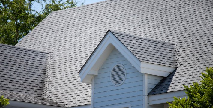 garret house and Roof shingles on top of the house among a lot of trees. dark asphalt tiles on the roof background