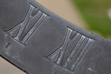 A metal sundial showing roman numerals of time