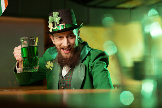 Dark-haired bearded young man in a leprechaun hat with shamrock looking funny