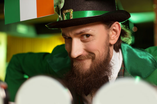 Dark-haired bearded young man in a leprechaun hat looking funny