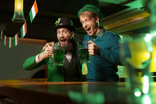 Dark-haired bearded young man in a leprechaun hat drinking beer with his friend