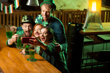 Company of good friends in st.patricks day costumes making selfie