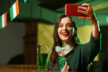 Long-haired cute girl in a green blouse making selfie on her smartphone