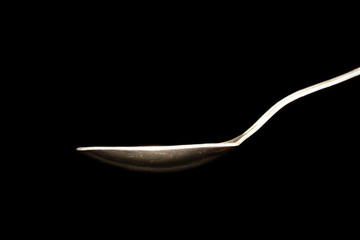 hot steel spoon on black background with steam from water