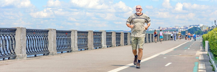 An elderly man runs along the river embankment, a healthy lifestyle.