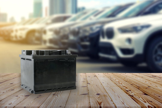 Car battery on wooden table on blurred car park row on background.