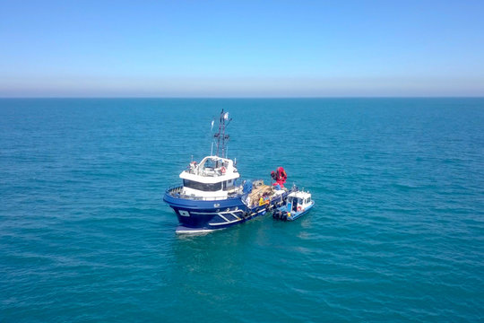 Fishing boat at sea with a smaller boat tied next to it - Aerial image.