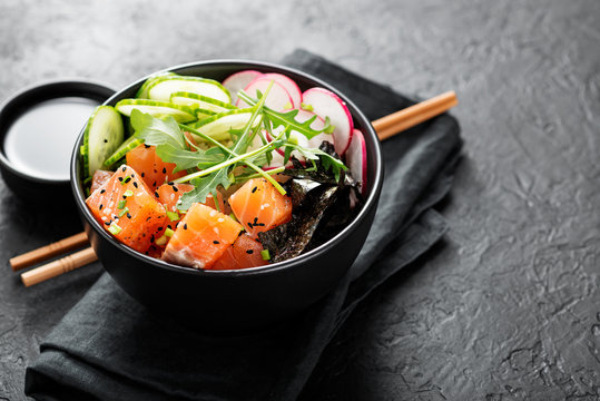 Salmon fish poke bowl with rice, radish,cucumber, tomato, sesame seeds and green onion.