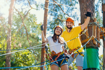 Young woman and man in protective gear are standing on rope bridge hanging on high trees, posing and smiling. Rope park with obstacles and ziplines. Extreme rest and summer activities concept. Wall mural