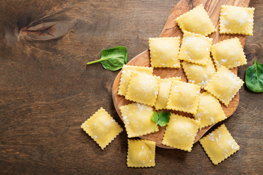 Tasty raw ravioli with flour and greens on dark background.
