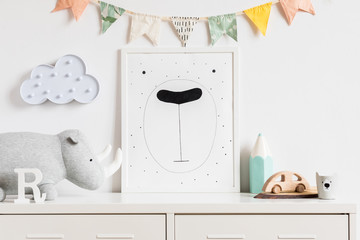 The modern scandinavian newborn baby room with mock up poster frame, wooden toy, plush rhino, accessoreis and clouds. Hanging cotton flags. Minimalistic and cozy decor of childroom. Mock up concept.