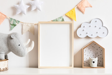 The modern scandinavian newborn baby room with mock up photo frame, wooden toy, plush rhino and clouds. Hanging cotton flags, white stars and cloud. Minimalistic and cozy decor of childroom.