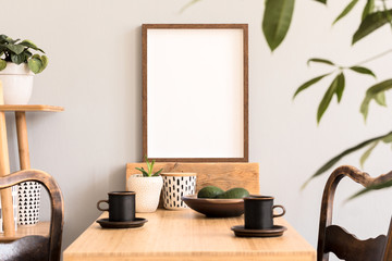 Stylish and sunny interior of kitchen space with wooden table with brown mock up photo frame, design chairs and bamboo shelf. Scandinavian room decor with kitchen accessories and beautiful plants.