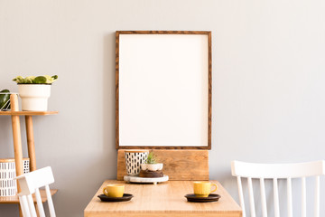 Stylish retro and sunny interior of kitchen space with wooden table with mock up photo frame, design furnitures and yellow cups. Scandinavian room decor with accessories, bamboo shelf and plants.