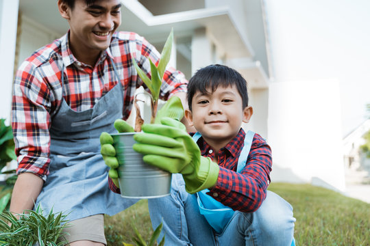 dad and son planting a plant gardening at their house together. parenting outdoor activity with son
