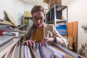 wide angle of attractive office woman working looking files in basement Wall mural