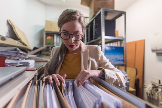 wide angle of attractive office woman working looking files in basement