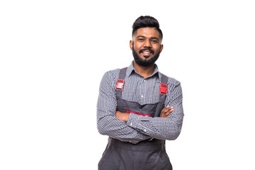 Portrait of cheerful indian repairer in shirt and overall having arms crossed looking at camera isolated on grey background Wall mural