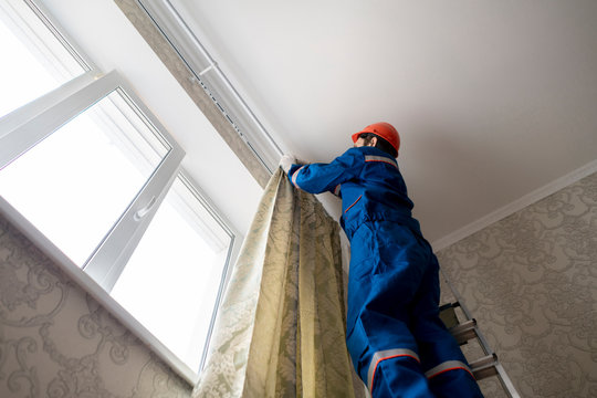 worker repairman hanging and fixing the curtain on the window f