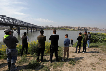 Iraqi people gather near the site where a ferry sank in the Tigris River in Mosul
