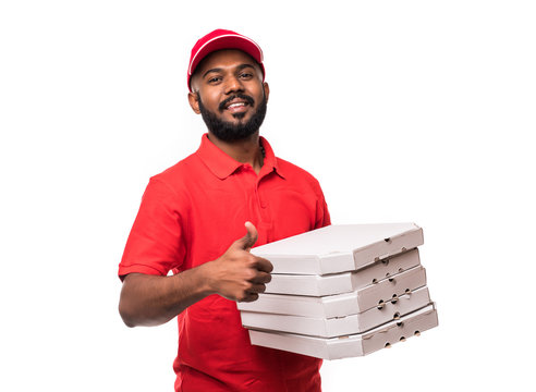Pizza delivery concept. Young handsome delivery man showing pizza box and holding thumb up sign isolated on white background
