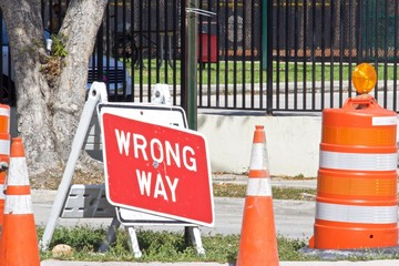 Orange traffic cones and Wrong Way Sign,Red background with white letters