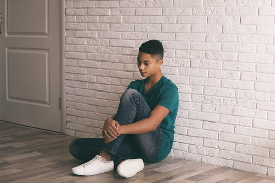 Upset African-American teenage boy sitting alone on floor near wall