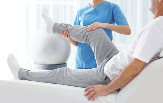 Doctor working with patient in hospital, closeup. Rehabilitation physiotherapy