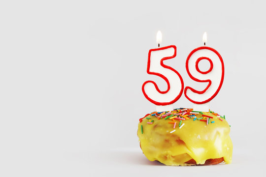 Fifty nine years anniversary. Birthday cupcake with white burning candles with red border in the form of 59 number. Light gray background with copy space