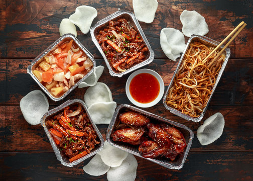 Chinese takeaway food. Crispy shredded beef, sweet and sour chicken wings, egg noodles with bean sprouts, pineapple, chilli dip and prawn crackers