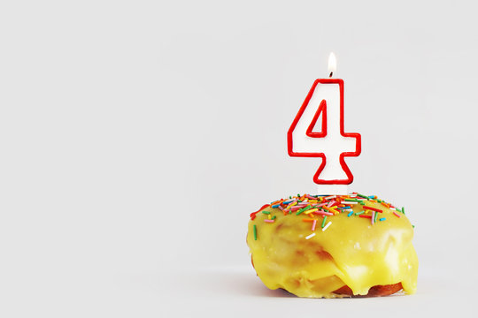 Four  years anniversary. Birthday cupcake with white burning candle with red border in the form of number Four. Light gray background with copy space