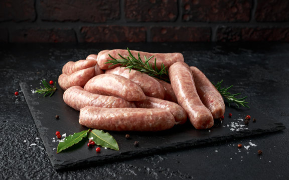 Freshly made raw butchers sausages in skins with herbs on stone board