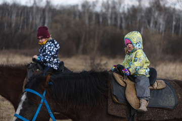 two little girl riding a horse