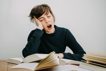 Gähnende Studentin sitzt am Schreibtisch vor ihren Büchern