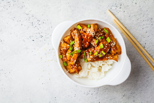 Teriyaki chicken with rice, sesame and green onions in white bowl.