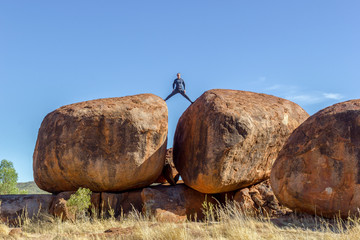 Man standing on Devils Marbels national park, outback Australlia, northern territory