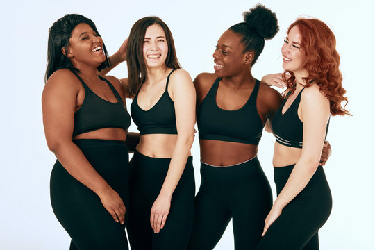 Group of women of different race, figure and size in sportswear standing together, chatting and laughing against white background.