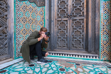 Young European tourist with a camera takes a picture in The Madrasa Bou Inania ( Medersa el Bouanania ) is acknowledged as an excellent example of Marinid architecture. Souk Medina of Fez, Fes el Bali