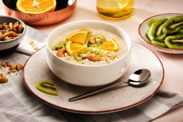 Oatmeal with fruit. Porridge with kiwi and orange. Healthy food. Tasty breakfast