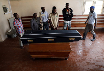 Family members stand over the coffin of Sumba Mufusho, who died after surviving for two days sheltering in a tree in the aftermath of Cyclone Idai, in Beira