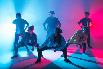 Group of diverse young hip-hop dancers in studio with special lighting effects in blue and pink...