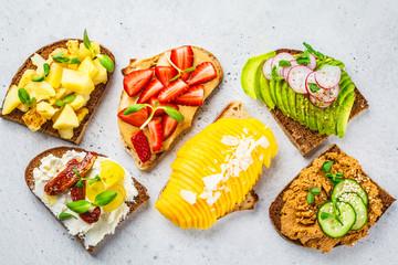 Sandwiches with mango, strawberry, tofu pate, avocado, potatoes and ricotta on a white background.