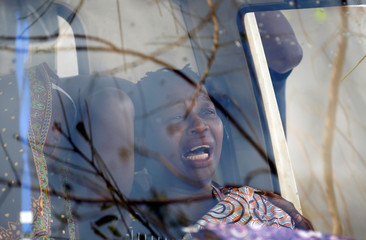 A family member of Sumba Mufusho, who died after surviving for two days sheltering in a tree in the aftermath of Cyclone Idai reacts in the car after collecting her body at a morgue
