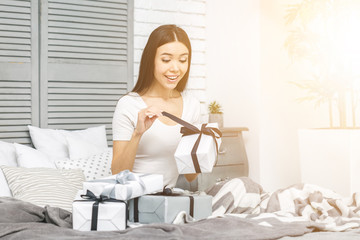 Smiling happy beautiful woman with gift boxes lying in bed. Morning surprise. Packing gifts. Online shopping.