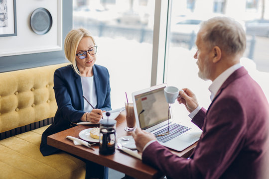 awesome woman in stylish clothes and old man having a business meeting.formal conversation in informal style